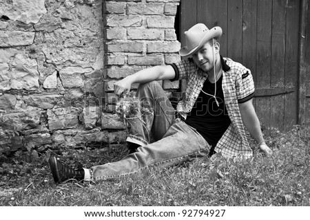 Handsome country man sitting on grass with flowers near the brick wall