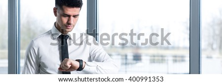 Handsome elegant man standing in office in corporation. Checking time on his watch