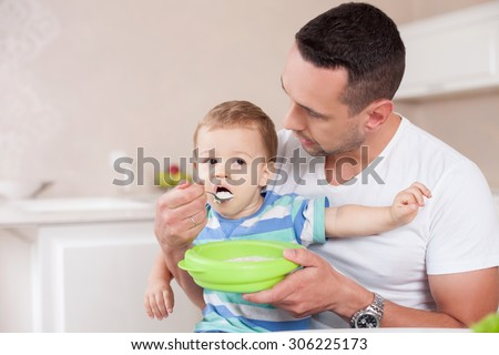 Handsome father is feeding his son with concentration. He is sitting in the kitchen and holding the boy on his knees. The toddler is eating porridge with appetite. Copy space in left side