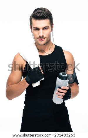 Handsome fitness man holding towel and bottle with water isolated on a white background. Looking at camera