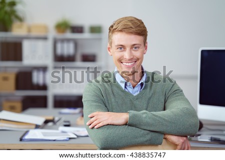 Handsome friendly young businessman sitting leaning on a table in the office looking at the camera with a beaming smile