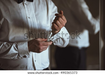 handsome groom prepares for ceremony
