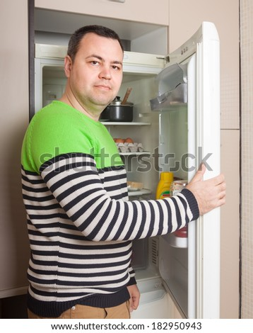 Handsome guy near opened refrigerator in kitchen at home