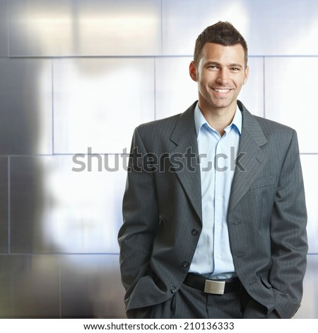 Handsome happy confident caucasian businessman hands in pocket, suit with no tie. Smiling, standing, looking at camera,
