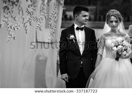 Handsome happy groom and beautiful blonde bride in white dress at the aisle outdoors close-up