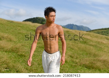 handsome Healthy man walking over mountain grass