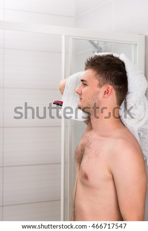 Handsome male dries his wet hair with a clean towel after washing procedures in the modern tiled bathroom