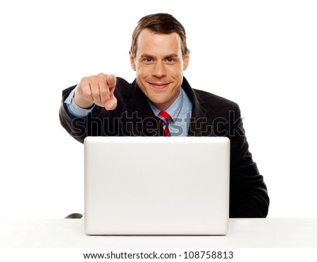 Handsome male executive pointing at you while working on laptop at his work desk