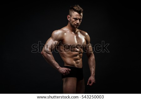 Handsome male model posing at studio in front of a black background.