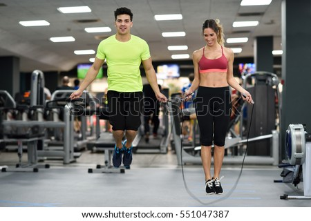 Handsome man and beautiful sporty woman workout with jumping rope in crossfit gym