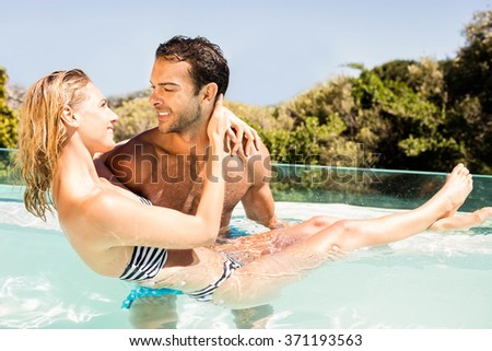 Handsome man carrying his girlfriend in the pool