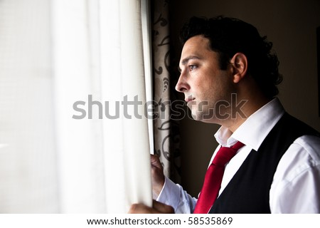 Handsome man dressed up looking through a window with worry