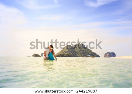 handsome man hold his beautiful blonde wife in elegant dress stand in water with green mountain on background