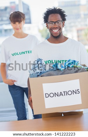 Handsome man holding donation box full of clothes next to a colleague