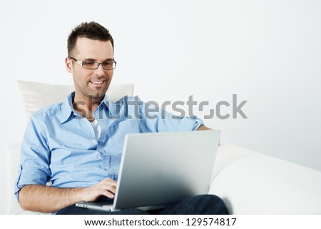 Handsome man in glasses using laptop on sofa