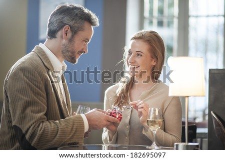 handsome man offering a gift to his girlfriend in a bar