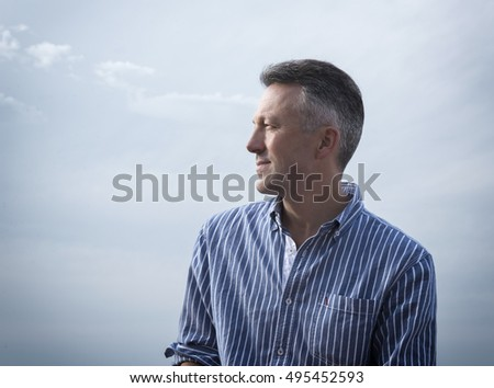 Handsome man. Outdoor male portrait. Middle-aged man over blue-gray dramatic sky, summer outdoor portrait, image toned.