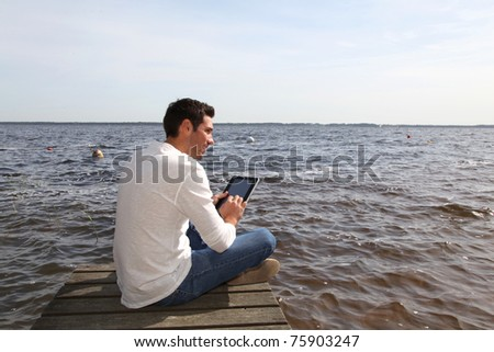 Handsome man sitting on a pontoon with touchpad