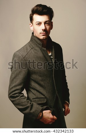 Handsome man wearing jeans clothes and a coat posing at studio. Toned image