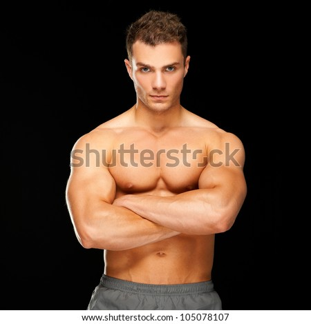 Handsome man with arms crossed looking his left on black background