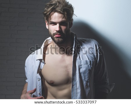 Handsome man with beard or blond muscular macho athlete bodybuilder in unbutton shirt with six packs and abs on muscle torso poses on white background