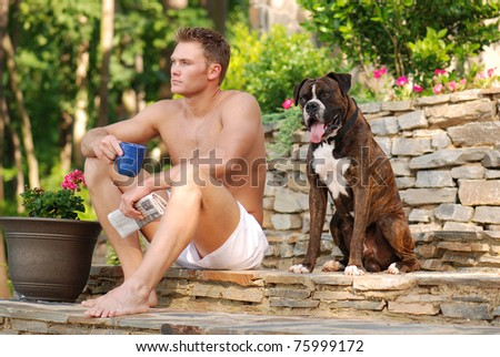 Handsome Man with Newspaper in Boxer Shorts Drinking Coffee with Boxer Dog