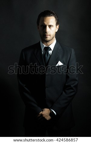 Handsome man with unshaven face and hairstyle in black formal suit with tie and white shirt and handkerchief in jacket pocket on studio background