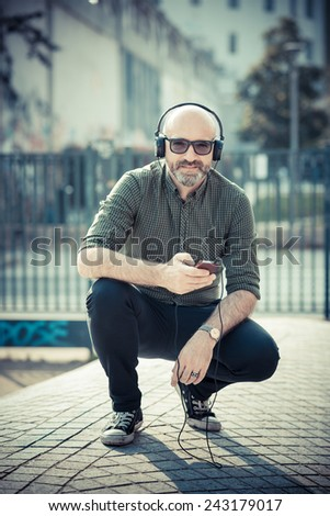 handsome middle aged man listening music in the city