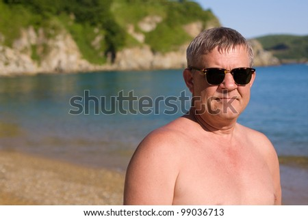 Handsome middle aged man sunbathes on the beach
