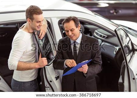 Handsome middle aged salesman is presenting a car to handsome young customer in a motor show