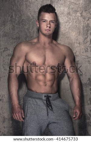 Handsome muscular guy against concrete wall