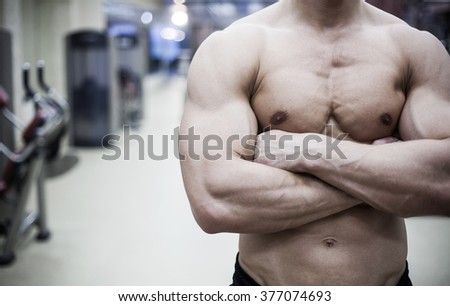 handsome muscular male body in gym. unrecognizable