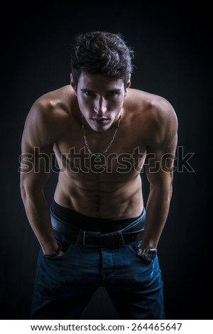 Handsome muscular shirtless young man standing confident leaning forward with hands in his pockets