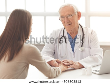 Handsome old doctor in white medical coat and eyeglasses is consulting his patient and holding her hand while sitting in his office