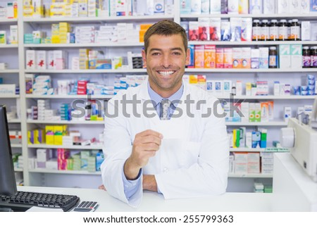 Handsome pharmacist holding paper at the hospital pharmacy