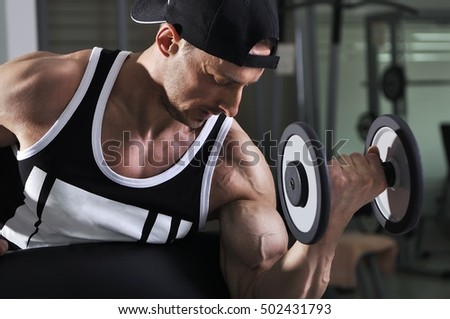 Handsome powerful athletic man doing biceps exercise with dumbbell. Strong bodybuilder with perfect muscles.