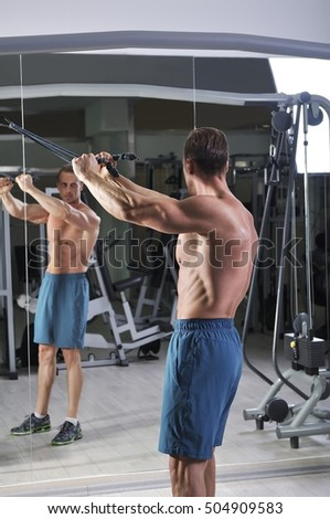 Handsome powerful athletic man doing exercise for back with cables. Strong bodybuilder with perfect abs, back and chest.