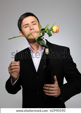 Handsome romantic young man holding rose flower and vine bottle ...