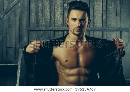 Handsome sexy sensual muscular stylish young man in leather jacket with bare torso standing indoor near stairs on wooden background, horizontal picture
