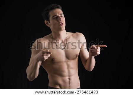 Handsome shirtless young man laughing and pointing fingers to a side, on black background