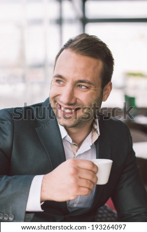Handsome smiling man drinking espresso in cafe