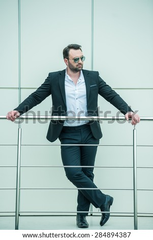 Handsome successful businessman standing on stairs of modern office.
