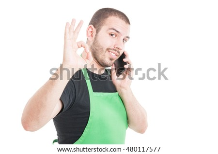 Handsome supermarket employee showing okay gesture isolated on white background with advertising area