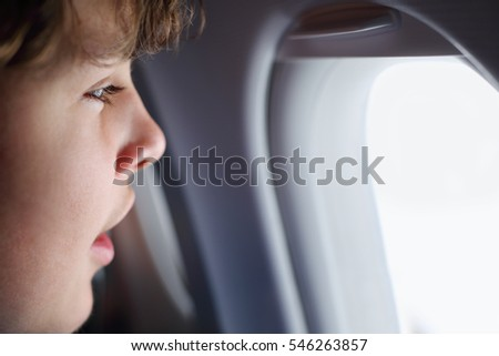 Handsome teenager boy looks into window in airplane during trip