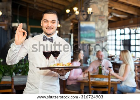 Handsome waiter in a white shirt wearing a bowtie showing ok sign in a restaurant