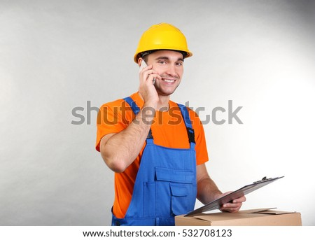 Handsome warehouse worker talking by mobile phone while standing near carton box, on light background