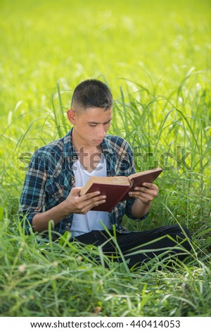 Handsome young boy in colorful shirt reading while lying on grass in green park