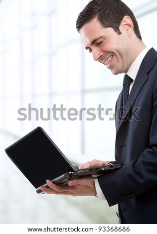 Handsome young business man in blue suit standing with laptop in office.
