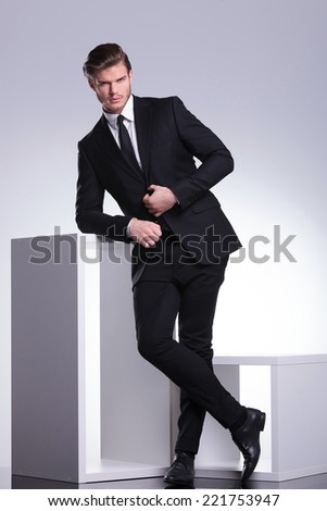 Handsome young business man looking at the camera while leaning on a white cube, closing his jacket with one hand.