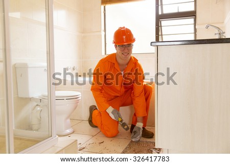 handsome young contractor removing old floor tiles in bathroom
